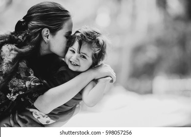 Young woman kisses charming little girl holding her on the arms