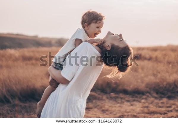 Молодая женщина целует своего маленького сына на солнечном лугу на закате. Молодая мать держит своего ребенка. Мать и маленький сын, хорошо проведя время на природе. Цвет тонированного изображения. День Матери. Концепция семьи