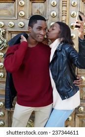 Young woman kissing her boyfriend on the cheek taking self-portrait picture with smart-phone, happy couple in love on honeymoon, dark skinned couple having romance taking picture with phone