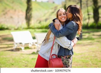 Young woman kissing her friend face outdoors. Blonde and brunette girls wearing casual clothes outdoors.