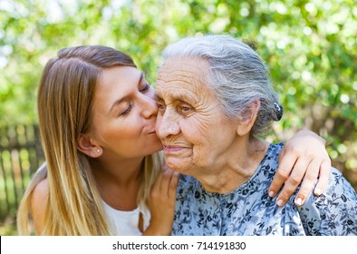 Young woman kissing her old grandmother in the park