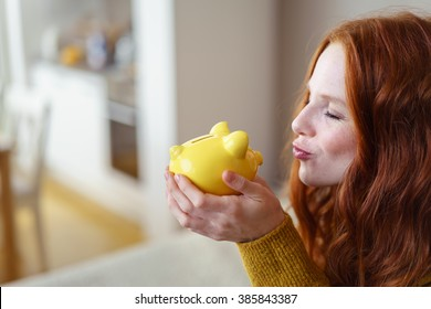 Young woman kissing her piggy bank with an expression of bliss as she cradles in it her hands while relaxing at home in a conceptual image