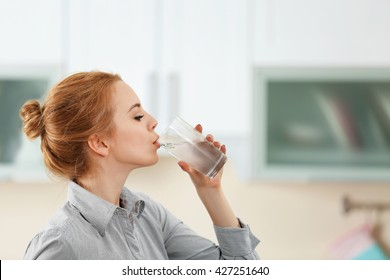 Young woman in the kitchen drinking water