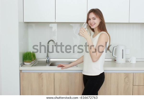 Young woman in the kitchen drinking water.