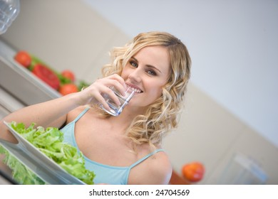 young woman in kitchen eating salad in kitchen