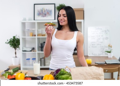 Young woman in the kitchen having healthy breakfast, eating wholesome sandwich with vegetables and glass of milk front view portrait