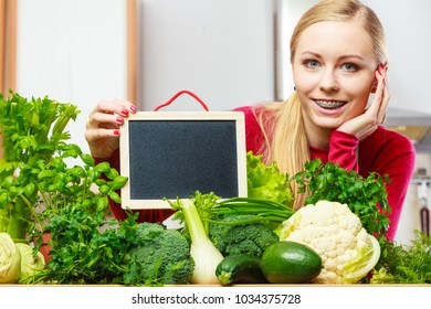 Young woman in kitchen having many green vegetables about to cook something healthy and vegetarian, holding blank black board for copyspace
