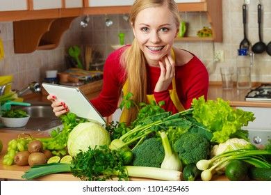 Young woman in kitchen having many green vegetables on table, holding tablet thinking about cooking something and searching for recipes in internet