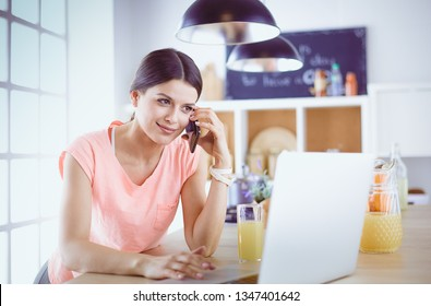 Young woman in kitchen with laptop computer looking recipes, smiling. Food blogger concept.