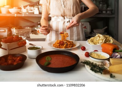 Young woman in kitchen making delicious pasta with sauce using a pan at home. Italian rural cooking still life. Wooden board, fresh vegetables, cooked pasta and a pan of sauce on wooden kitchen table.