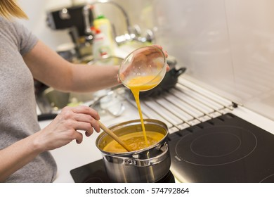 Young woman in the kitchen preparing eggs.