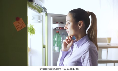 Young woman in the kitchen, she is looking into the fridge and thinking with hand on chin, food preparation and lifestyle concept