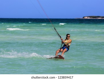 A young woman kite-surfer rides in greenish-blue sea under clear skies