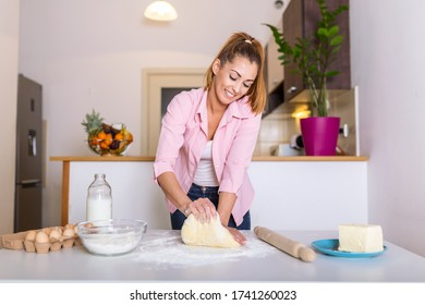 Young woman knead dough at kitchen, homemade bakery making. Woman kneading dough on kitchen table - Shutterstock ID 1741260023