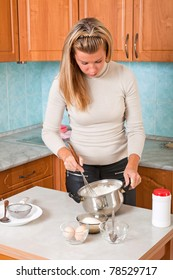 Young woman kneads dough in a pot