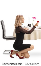 Young woman kneeling and proposing with a ring at a restaurant table isolated on white background