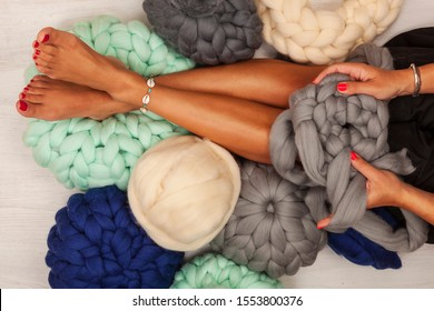 Young woman knit chunky merino pouf. Handmade chunky knitting. Winter fashion lifestyle.