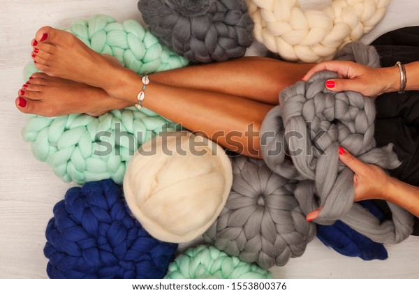 Young woman knit chunky merino pouf. Handmade chunky knitting. Winter fashion lifestyle.