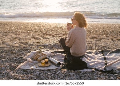 Young woman in knitted sweater having picnic at beach with tea in thermos and fresh baguettes in wicker eco bag. Cozy slow lifestyle concept.
