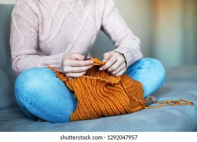Young woman knitting at home