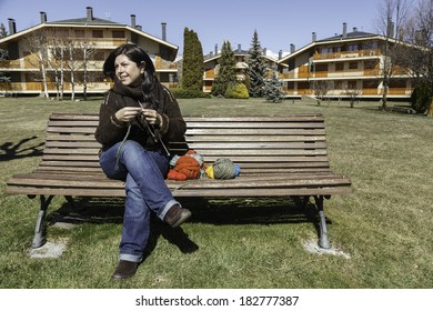 A young woman knitting in a park / Knitting in the park