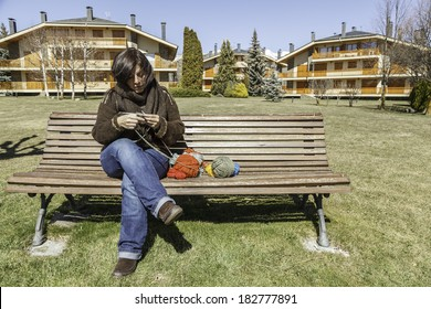 A young woman knitting in a park / Knitting outdoor