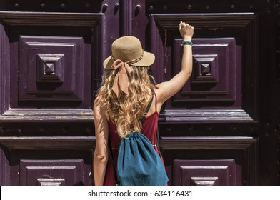 Young woman knocking the big old wooden doors