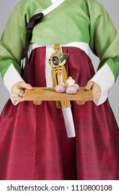 young woman in korean traditional clothing holding cutting board