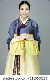 young woman in korean traditional clothing holding gift box