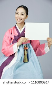 young woman in korean traditional clothing holding sign