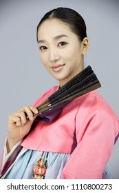 young woman in korean traditional clothing holding folding fan