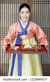 young woman in korean traditional clothing holding table service