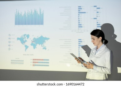Young woman in lab coat checking information on tablet while presenting ecological project at conference