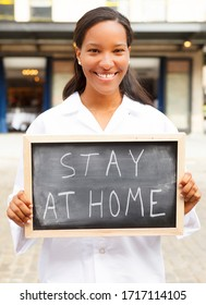 """A young woman in a lab coat holds a chalkboard with the words """"STAY AT HOME""""."""