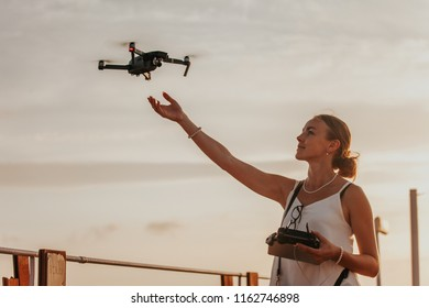 Young woman landing a drone on her hand by the seaside, holding remote control in her hard, sunset in the background