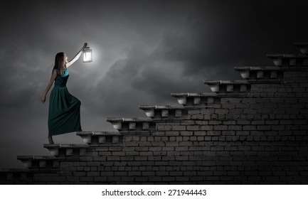Young woman with lantern walking in darkness