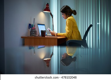 Young woman with laptop computer for homework. Tired hispanic girl and college education. Female student studying and using pc at home