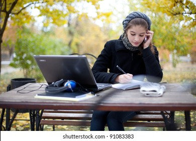 young woman with laptop computer in park