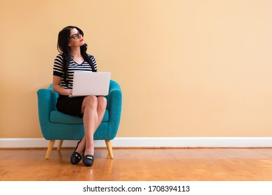 Junge Frau mit einem Laptop-Computer in einer nachdenklichen Pose sitzend im Stuhl