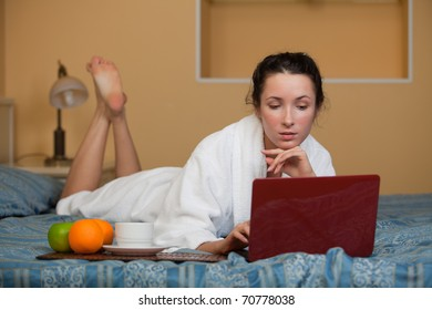 Young woman with laptop lies on the bed at home.