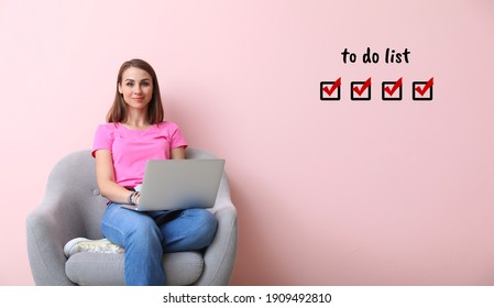 Young woman with laptop making to do list at home
