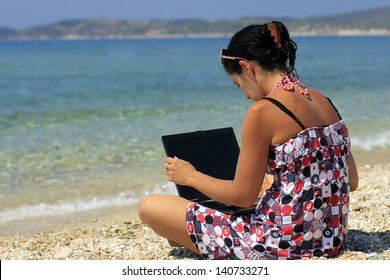 Young woman with laptop on the beach