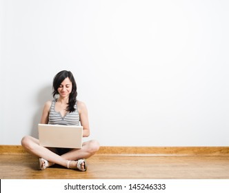 Young woman with a laptop on a wood floor