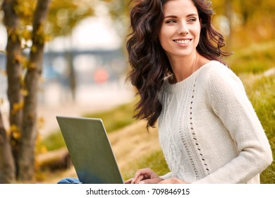 Young woman with laptop outdoors. - Shutterstock ID 709846915