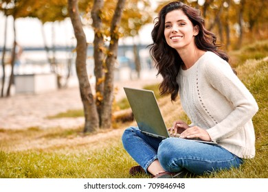 Young woman with laptop outdoors.