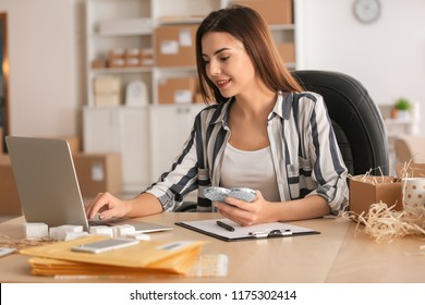 Young woman with laptop preparing parcel for shipment to client in home office