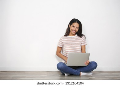 Young woman with laptop sitting on floor near light wall