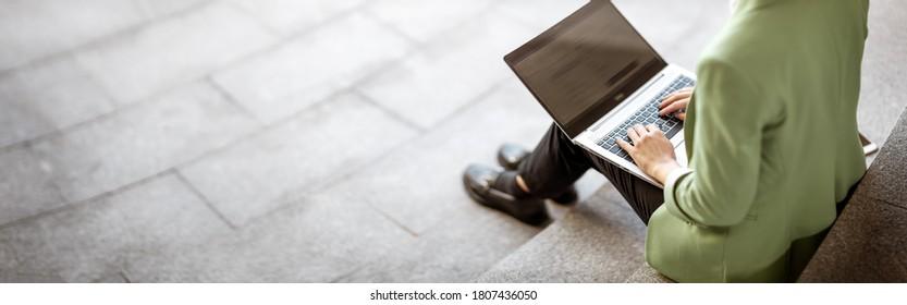 junge Frau mit Laptop, die auf der Treppe sitzt. Person, die im Freien den PC benutzt
