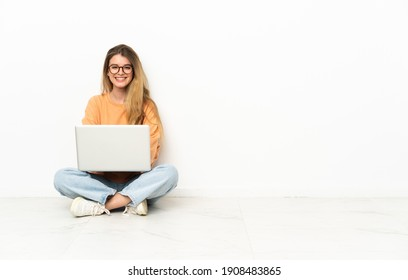 Young woman with a laptop sitting on the floor keeping the arms crossed in frontal position