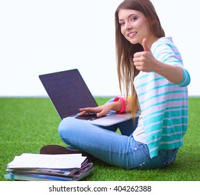 Young woman with laptop sitting on green grass and showing ok